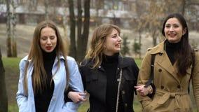 M?dchenhafte Freundschaft Drei junge schöne Mädchen gehen in den Stadtpark Sie sind gl?cklich Mädchen sind glücklich sich zu tref stock footage