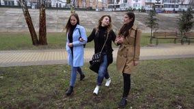 M?dchenhafte Freundschaft Drei junge sch?ne M?dchen gehen in den Stadtpark Sie sind gl?cklich M?dchen sind gl?cklich sich zu tref stock video footage