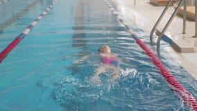 M?dchenkind im Swimmingpool L?chelndes Kind f?hrt einen gesunden Lebensstil und scharfes auf Sport stock footage