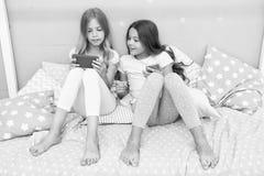 M?dchenschwestern tragen den Pyjama, der mit Smartphones besch?ftigt ist Kinder im Pyjama wirken auf Smartphones ein Anwendung f? stockfotos