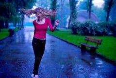 M?dchentanzen und R?tteln des Haares unter dem Regen stockfoto