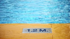 1.2 M.Depth marking on pool edge.inscription of the swimming pool depth.pool depth sign stock video footage