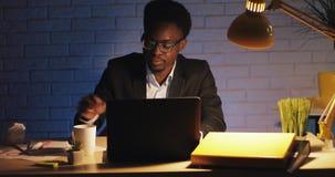 M?der B?roangestellter, der an dem Laptop an Sp?t- arbeitet Gähnender und trinkender Kaffee er Ein Geschäftsmann ist in allein stock video