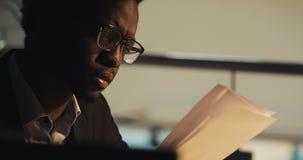M?der junger schwarzer Gesch?ftsmann, der mit Dokumenten im Nachtb?ro arbeitet Gesch?ft, Workaholic, Fristenkonzept stock footage