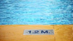 1 2 m diepte die op poolrand merken inschrijving van de zwembaddiepte Het teken van de pooldiepte stock videobeelden