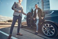 M?drze atrakcyjny biznesmen wychodzi od samochodu podczas gdy jego asystent otwiera drzwi dla on obraz stock