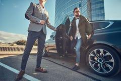 M?drze atrakcyjny biznesmen wychodzi od samochodu podczas gdy jego asystent otwiera drzwi dla on obrazy royalty free