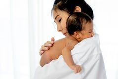 A m?e asi?tica com lugar branco da camisa em cima do ombro de pouco beb? rec?m-nascido ap?s d? o leite e o beb? olha sonolento foto de stock royalty free