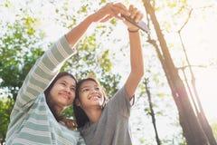 M?e asi?tica e filha que tomam um selfie no parque imagem de stock