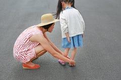 M?e asi?tica que ajuda sua filha pequena a p?r sapatas sobre a estrada exterior imagem de stock