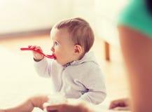 M?e e beb? com colher que comem em casa fotos de stock royalty free