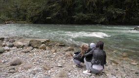 M?e com as duas crian?as da crian?a que jogam fora pelo rio da montanha video estoque