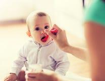M?e com a colher que alimenta o beb? pequeno em casa fotos de stock