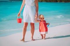 M?e e filha pequena bonito que andam na praia foto de stock