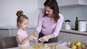 M?e e filha que cozinham junto na cozinha Menina que quebra o ovo na bacia Pastelaria de cozimento da fam?lia feliz em video estoque