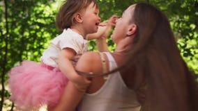A m?e feliz abra?a a filha pequena ador?vel e gerencie com ela no parque ensolarado video estoque