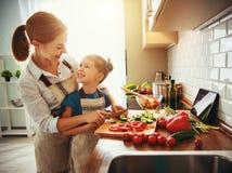 M?e feliz da fam?lia com a menina da crian?a que prepara a salada vegetal foto de stock