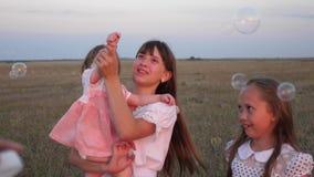 M?e feliz que joga com as crian?as que fundem bolhas de sab?o as crian?as travam bolhas e riso no parque no ver?o lento vídeos de arquivo