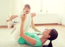M?e feliz que joga com beb? em casa imagem de stock royalty free