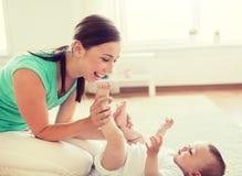 M?e feliz que joga com beb? pequeno em casa imagem de stock royalty free