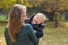 M?e feliz que joga com seu filho no parque fotografia de stock