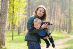 M?e feliz que joga com seu filho no parque foto de stock