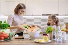 A m?e e a filha que cozinham junto na salada, no pai e na crian?a vegetais da cozinha est?o falando o sorriso imagem de stock