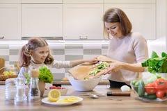 A m?e e a filha que cozinham junto na salada, no pai e na crian?a vegetais da cozinha est?o falando o sorriso imagens de stock
