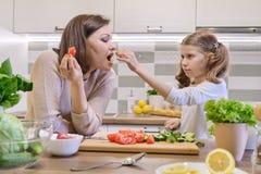A m?e e a filha que cozinham junto na salada, no pai e na crian?a vegetais da cozinha est?o falando o sorriso foto de stock