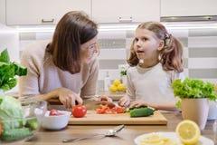 A m?e e a filha que cozinham junto na salada, no pai e na crian?a vegetais da cozinha est?o falando o sorriso fotos de stock royalty free