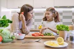 A m?e e a filha que cozinham junto na salada, no pai e na crian?a vegetais da cozinha est?o falando o sorriso fotos de stock