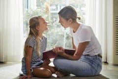 M?e e filha que discutem o livro imagens de stock royalty free