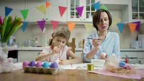 M?e e filha que sentam-se na tabela e que crafting o ninho com ovos coloridos junto e que luaghing na cozinha vídeos de arquivo