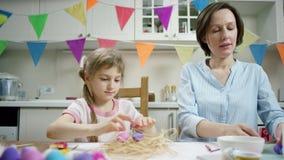 M?e e filha que sentam-se na tabela e que crafting o ninho com ovos da p?scoa coloridos junto e que luaghing na cozinha video estoque