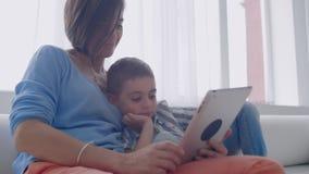M?e e filho que jogam com tabuleta digital em casa Mãe nova com seus 5 anos do sorriso velho com a tabuleta digital em filme