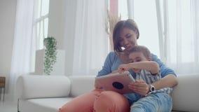 M?e e filho que sentam-se em Sofa Using Digital Tablet Mamã e rapaz pequeno felizes que usa a tabuleta com écran sensível junto vídeos de arquivo