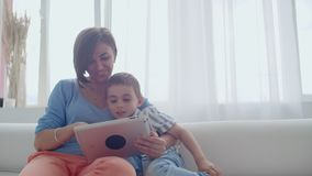 M?e e filho que sentam-se em Sofa Using Digital Tablet Mamã e rapaz pequeno felizes que usa a tabuleta com écran sensível junto video estoque