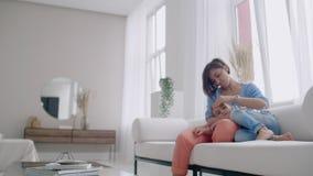 M?e e filho que usa a tabuleta que olha a tela e que fala no sof? na casa acolhedor filme