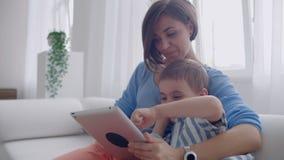 M?e e filho que usa a tabuleta que olha a tela e que fala no sof? na casa acolhedor video estoque