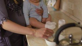 M?e gr?vida que cozinha com seu filho do beb? na cozinha e que tem o divertimento - azul vestindo do menino misturado asi?tico da video estoque