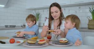 M?e nova bonita com os dois filhos das crian?as no cozinheiro claro branco do kuna com hamburgueres vídeos de arquivo
