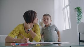 M?e nova bonita em uma camiseta morna que encontra-se no assoalho com meu desenho do filho com os marcadores no papel que retrata video estoque