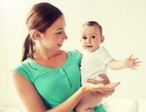 M?e nova feliz com beb? pequeno em casa fotos de stock