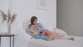 M?e nova feliz que mostra desenhos animados na tabuleta digital a seu filho da crian?a antes de ir dormir video estoque