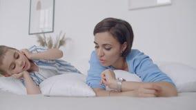 M?e nova feliz que mostra desenhos animados na tabuleta digital a seu filho da crian?a antes de ir dormir Exibição feliz da mãe video estoque