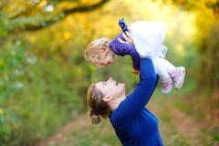 M?e nova feliz que tem a filha bonito da crian?a do divertimento, retrato da fam?lia junto Mulher com o beb? bonito na natureza imagens de stock royalty free