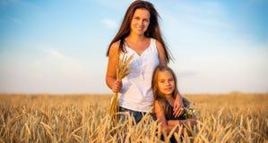 M?e nova e sua posi??o da filha no campo de trigo no por do sol fotos de stock