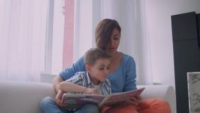 A m?e e o filho leram livros A m?e e o filho novos felizes leram livros no sof? em casa filme