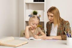 M?e que ensina a filha pequena Fazendo o conceito dos trabalhos de casa em casa foto de stock royalty free