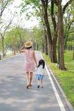 M?e e sua filha que andam na estrada e que guardam as m?os no jardim exterior da natureza Vista traseira foto de stock royalty free